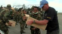 Aid workers and soldiers unload boxes