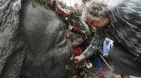 Woman places flowers on a monument