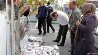Iranians look at newspapers in Tehran
