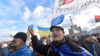 People shout slogans and wave flags of Ukraine and the European Union during a rally of the opposition on Independence Square in Kiev on December 2, 2013