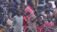 Crowds standing behind razor wire