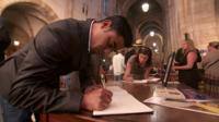 Congregants sign books of condolence at St George's Cathedral in Cape Town