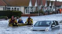 Rescuers take people to safety on a lifeboat