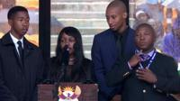 The sign language interpreter (far right) signs tributes by Nelson Mandela's grandchildren