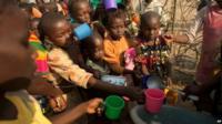Children crowding round volunteer to collect rice porridge