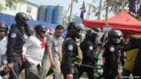 Police and civilians move in to clear the Phnom Penh park