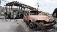 View of a burnt bus and car at Vida Nova