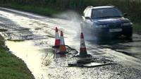 Car going through pothole