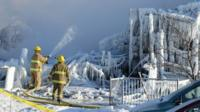 Canadian fire-fighters douse the burnt remains of a retirement home in L'Isle-Verte