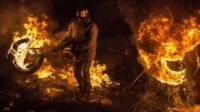Activists of Euromaidan (the name given for Independence Square) burn tyres and warm themselves at a barricade in the center of Kiev early on January 24, 2014