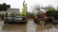 A passenger on a vintage tractor driving through flood water near Langport in Somerset