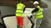 Workmen preparing sandbags