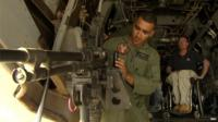 US Marine gunner, Hernandez, demonstrates weaponry on board MV-22 Osprey aircraft