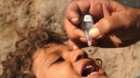 An Afghan health worker administers a polio vaccination to a child in Herat, Afghanistan, October 2013