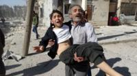 A man carries a wounded child after an air strike in Aleppo