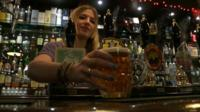 Woman putting pint of Phipps ale on bar in pub