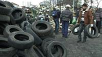 Protester carrying tyres to pile of tyres
