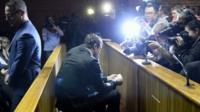 Oscar Pistorius surrounded by cameras in court