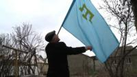 Rasim Bekirov with the flag of the Crimean Tatar people