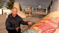 Steve Rosenberg standing by 'tank trap' with map of area on it