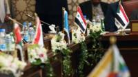 A Syrian flag (C) is displayed next to the empty Syrian seat during the opening session of the Arab League Foreign Ministers' meeting in Kuwait City on March 23