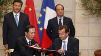 Xi Jinping (back left) and Francois Hollande (back right) watch documents being signed