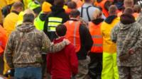Workers and volunteers observe a moment of silence outside of the Oso Fire Department at 10:37 a.m. Saturday, March 29