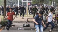 People run as riot police officers try to disperse protesters