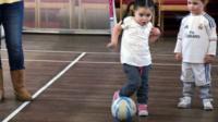 Girl kicks a football
