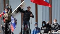 Pro-Russian activists who seized the main administration building in the eastern Ukrainian city of Donetsk hold Russian flag and flag of so-called Donetsk Republic
