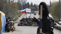 A pro-Russian militiaman gestures and holds a stick as he guards a barricade bearing the Russian flag