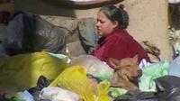 Woman and dog amongst rubbish bags