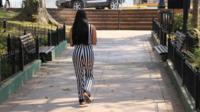 Woman walking away from camera along a path