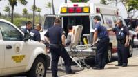 16-year-old boy, seen sitting on a stretcher centre, who stowed away in the wheel well of a flight from San Jose, Calif., to Maui is loaded into an ambulance at Kahului Airport in Kahului, Maui, Hawaii