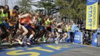 Elite men runners leave the start line