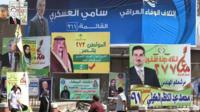 Iraqis walk past election posters in Baghdad (13 April 2014)