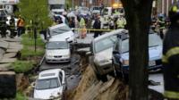 Cars sit on the edge of a sinkhole in the Charles Village neighborhood of Baltimore, Wednesday, April 30
