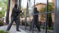 A Pro-Russian activists breaks the glass of the offices of Industrial Union of Donbass Corporation in Donetsk