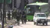 A bus starts to evacuate people from Homs