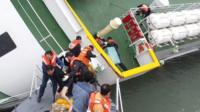 "This screen grab taken from a video released by Korea Coast Guard on April 28, 2014 shows the sunken South Korean ferry ""Sewol"" captain Lee Joon-Seok (L), wearing a sweater and underpants, being rescued from the tilting vessel"