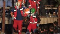 A miner is carried to an ambulance by rescuers