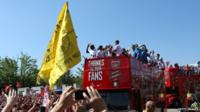 Players on board open top bus