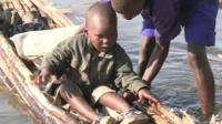 Child gets to dry land in flooded Nakuru National Park