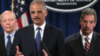 U.S. Attorney General Eric Holder (C) speaks as Deputy Attorney General James Cole (R) and IRS Commissioner John Koskinen (L) listen during a news conference