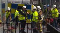 Firefighters begin to remove items from the Charles Rennie Mackintosh building