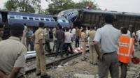 Indian officials and rescuers gather around the wreckage after the Gorakhpur Express passenger train slammed into a parked freight train Chureb, near Basti, Uttar Pradesh state