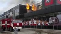 "A boy walks by as firefighters attempt to extinguish a fire at the sports arena Druzhba , which is the home venue of the ice hockey club ""Donbass"", in Donetsk"