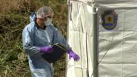 Forensic officer outside white tent