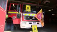 A fire engine with picket line signs