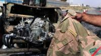 A man displays an Iraqi army jacket in front of a burnt out US-made Iraqi army HUMVEE vehicle at the Kukjali Iraqi Army checkpoint, some 10km of east of the northern city of Mosul, 11 June 2014